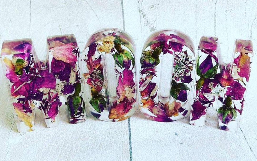 clear resin letters with purple flowers within spelling MOON